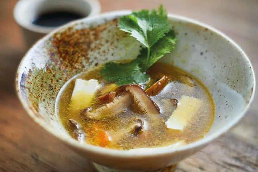 close up of tofu mushroom soup in rustic bowl