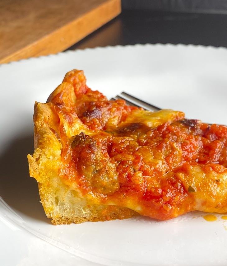 closeup deep-dish pizza slice showing edge of dough