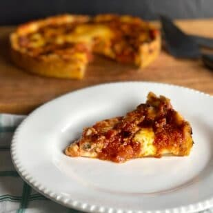 deep-dish low FODMAP pizza on board wedge cut out; wedge on white plate