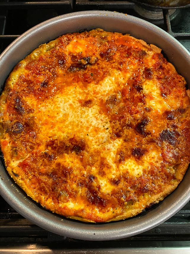 deep-dish pizza in pan right out of oven, on top of stove
