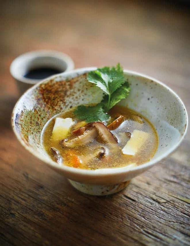 mushroom tofu soup in rustic bowl