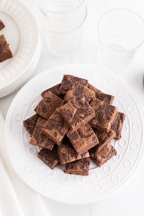 overhead view pyramid stack of low FODMAP Nutella Brownies on white plate, white background
