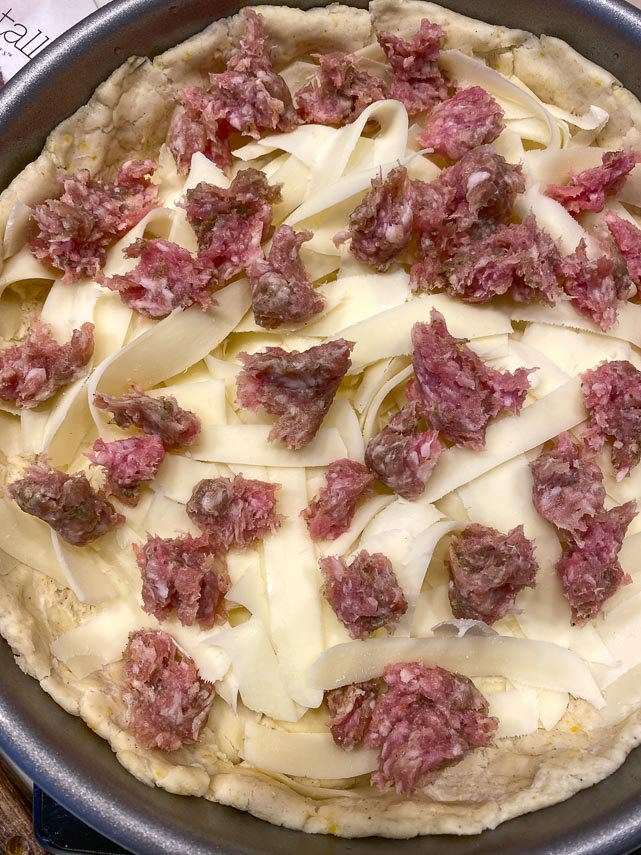 placing small pieces of raw sausage on deep dish pizza, before baking