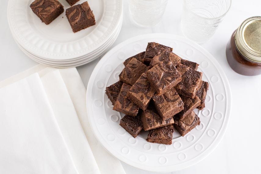 pyramid stack of low FODMAP Nutella Brownies on white plate, white background; Nutella in mason jar