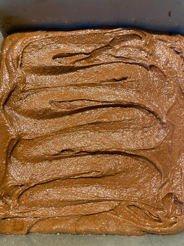 raw brownie batter in pan, top smoothed with icing spatula