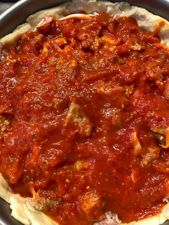 sauce added to deep dish pizza, before baking