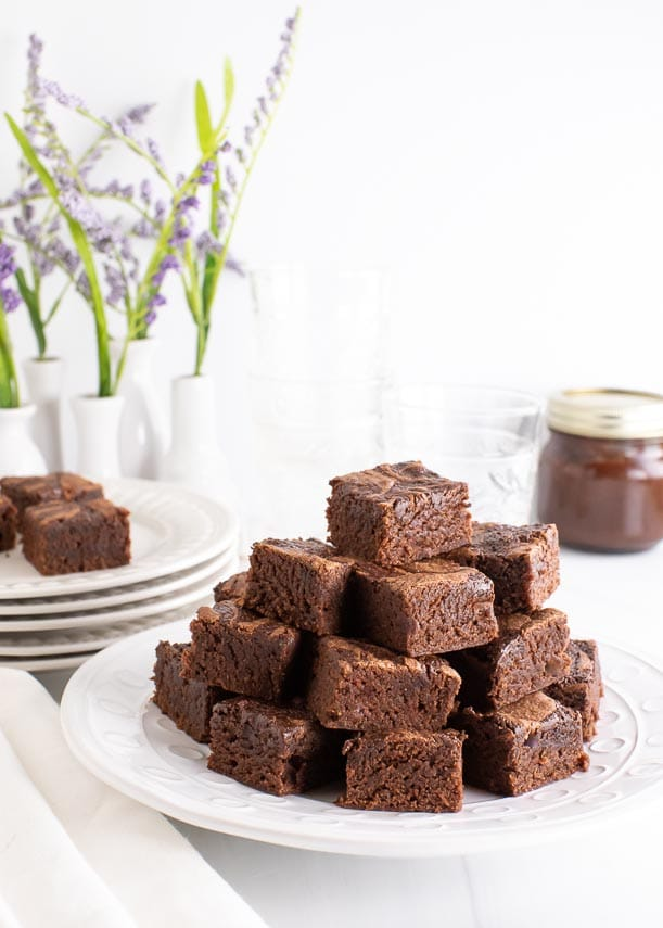 side shot of pyramid stack of low FODMAP Nutella Brownies on white plate, white backgroundl purple flowers in white vase