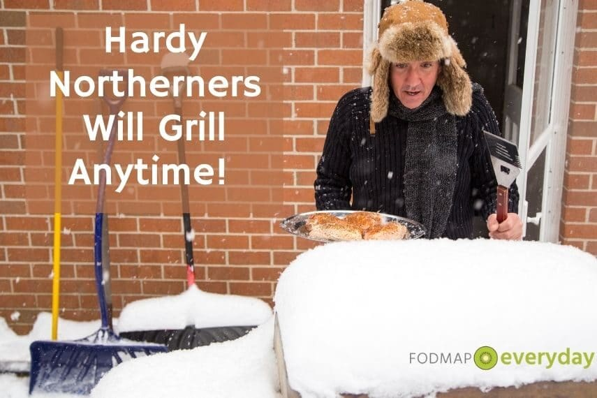 A man all bundled up holding a plate of food to put on a grill covered in snow.