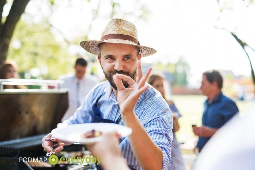 """a photo of a man making the sign """"perfecto!"""" with his fingers as he is handing a plate of food"""