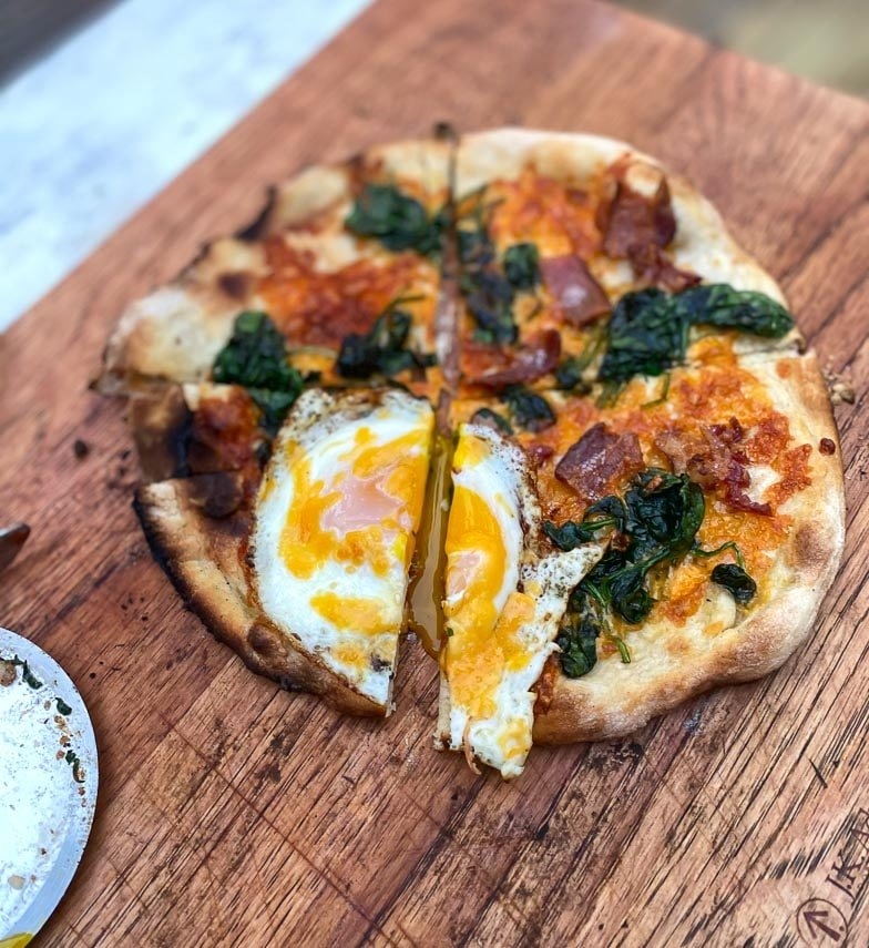 Breakfast pizza with egg, spinach and bacon on wood board; egg cut open