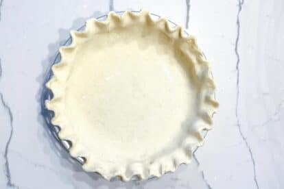 Cream cheese pie crust in pie plate, fluted edge on marble surface-2