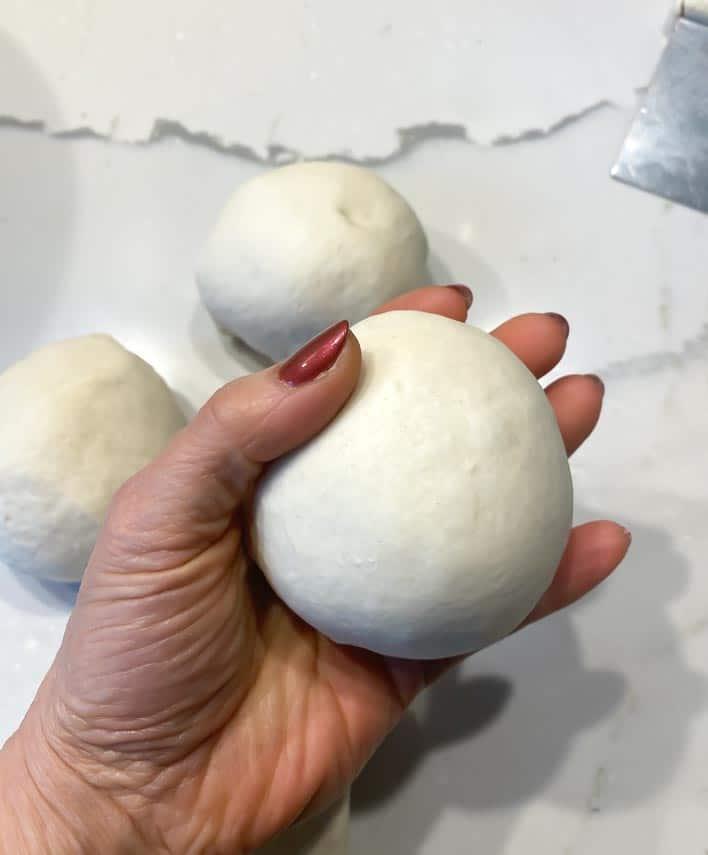 Making round dough balls out of Neapolitan pizza dough