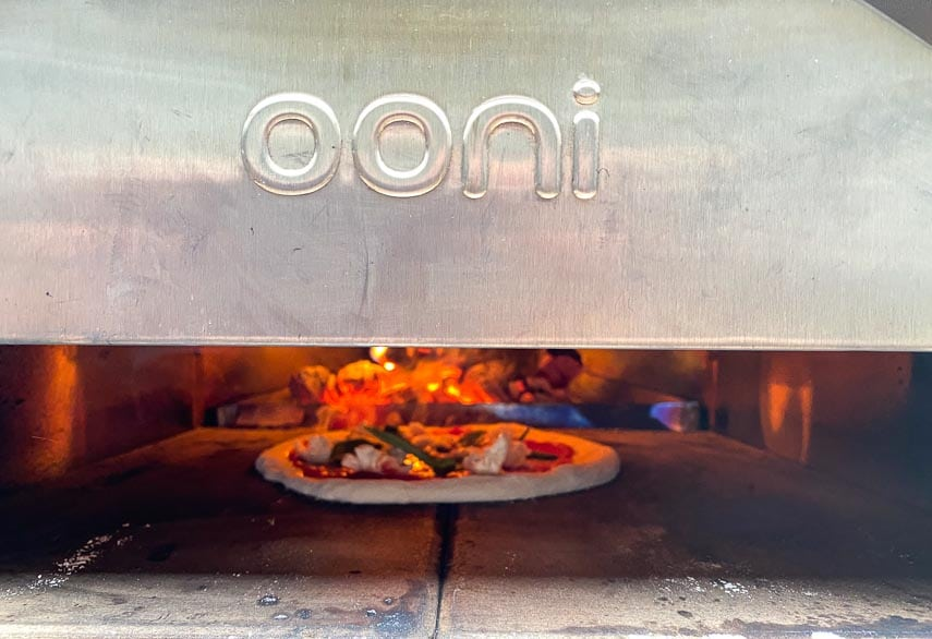 Ooni pro pizza door attached; pizza inside cooking