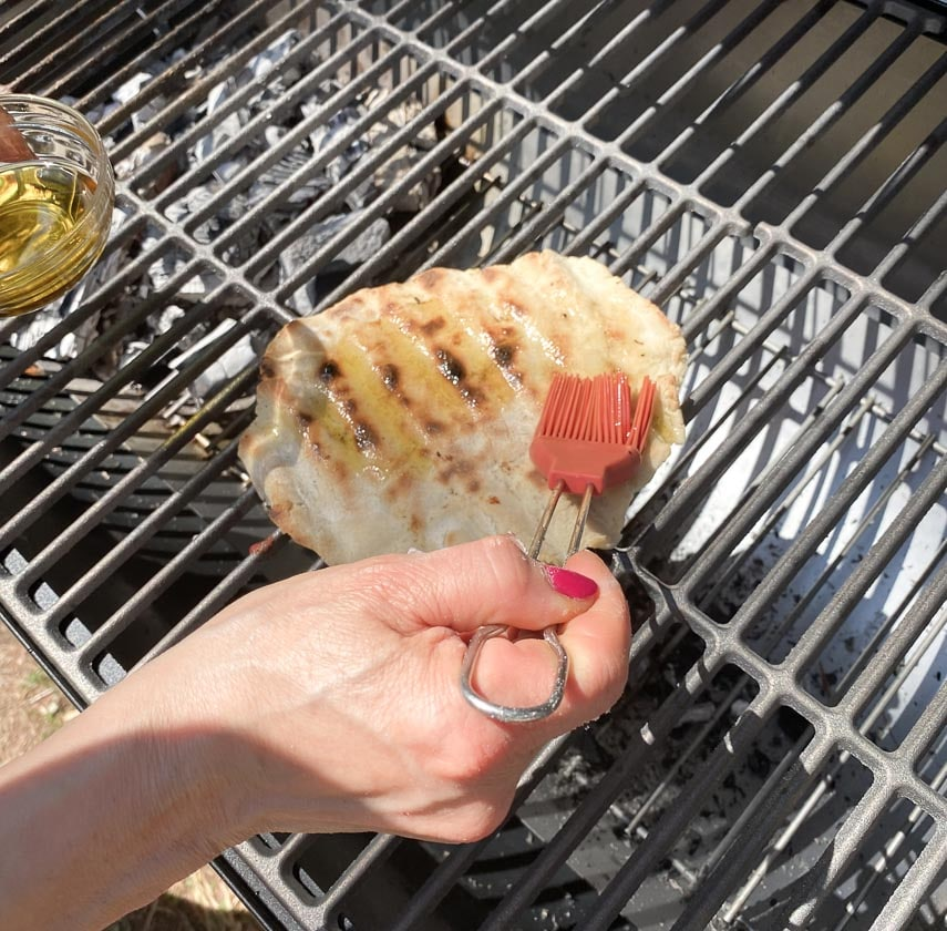brushing grilled pizza crust with garlic-infused oil