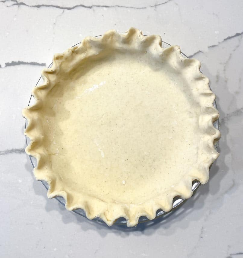 cream cheese pie crust in pie plate, fluted edge on marble surface