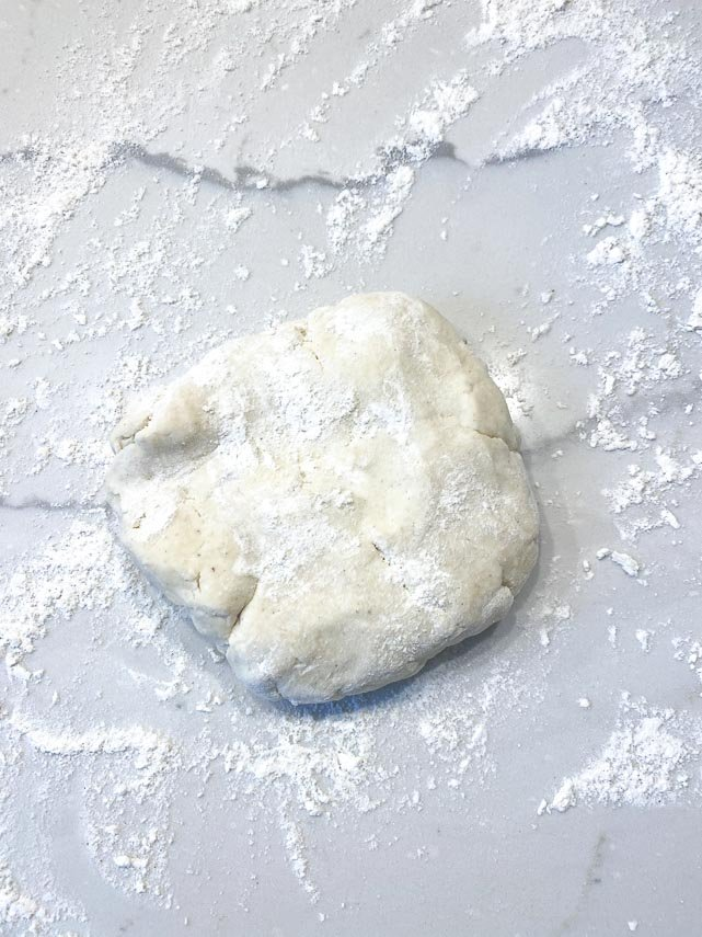 disc of cream cheese dough ready to roll out on lightly floured surface