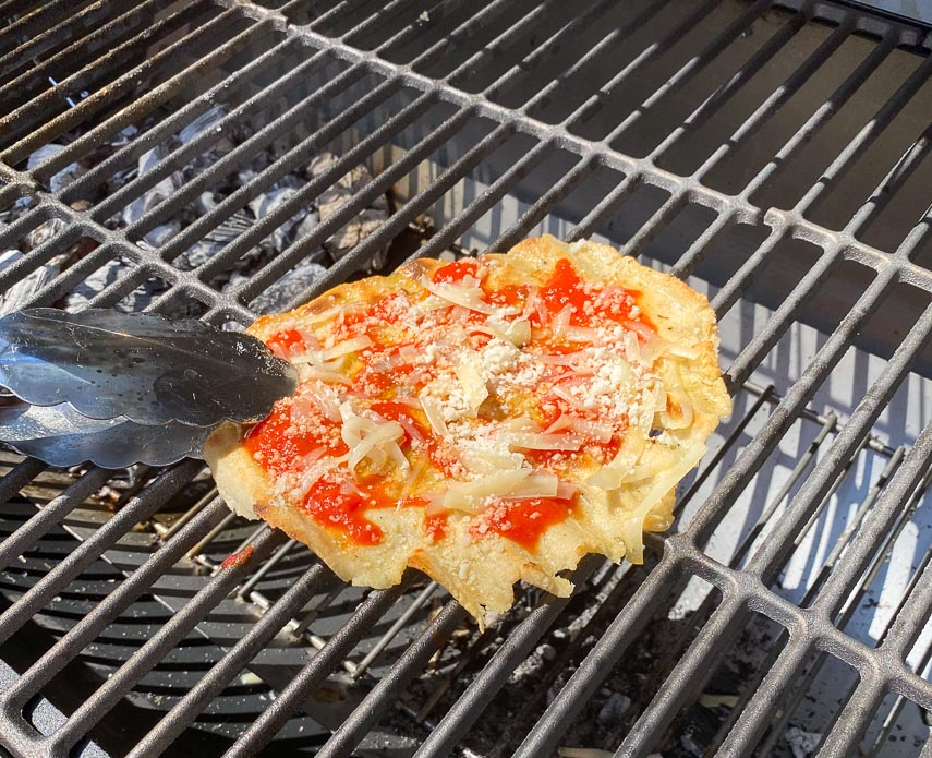 dragging grilled pizza back over coals with tongs