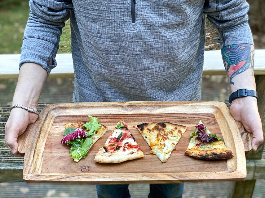 four kinds of low FODMAP pizza cut in wedges on wooden tray held by young man