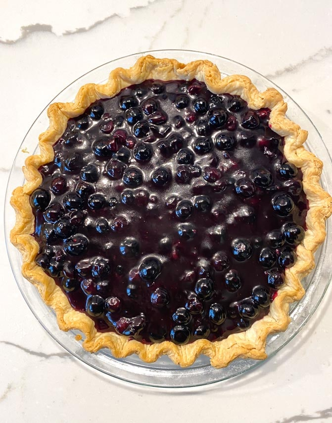 fresh blueberry pie on crust on marble surface