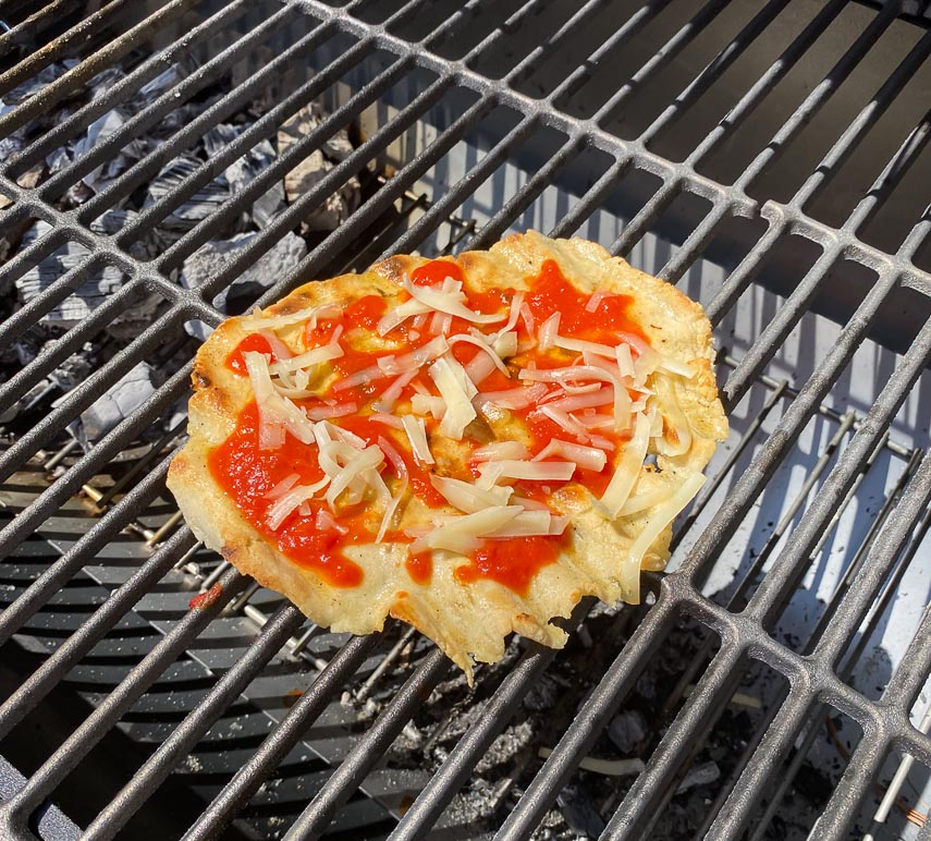 grilled pizza dolloped with tomato sauce and Fontina on grill