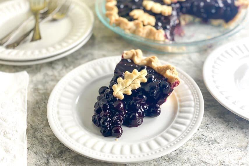 horizontal image of low FODMAP Fresh Blueberry Pie on white gray quartz and white plate 1