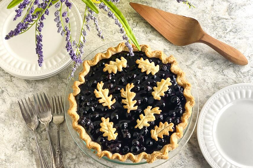 horizontal image overhead of low FODMAP Fresh Blueberry Pie on gray quartz with white plates, silver forks