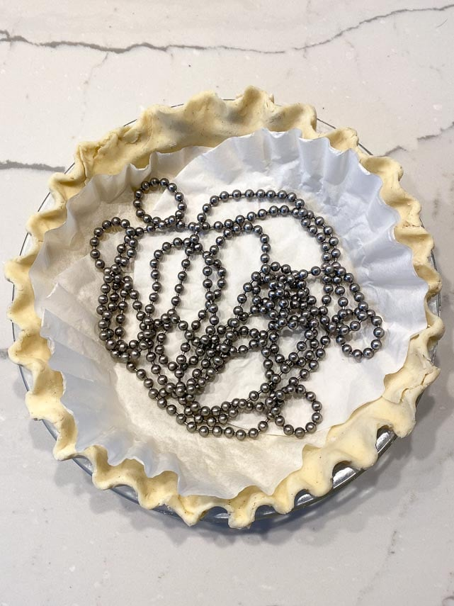 lining unbaked pie crust with coffee filters and pie weights on marble counter