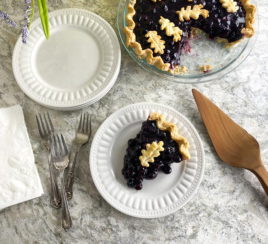 overhead image of low FODMAP Fresh Blueberry Pie on white gray quartz and white plate