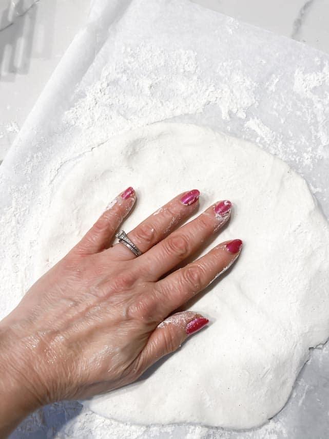 patting out Caputo GF pizza dough on floured parchment paper