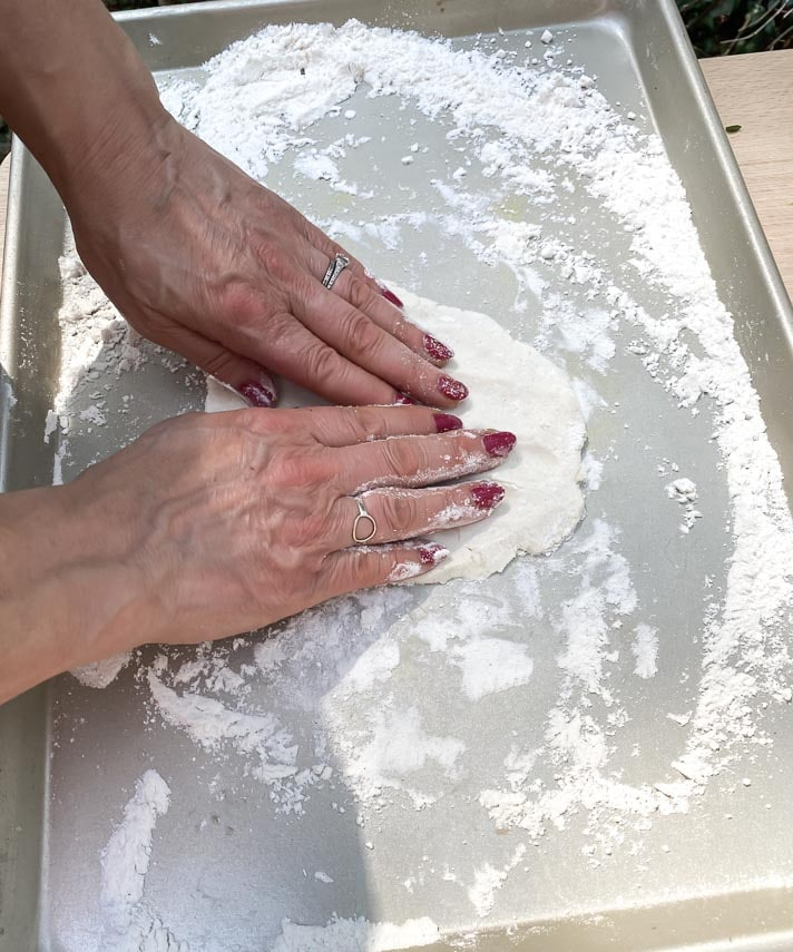 patting out grilled pizza dough in floured pan