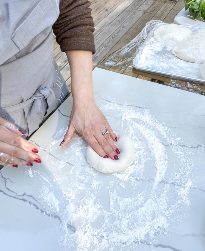 patting out pizza dough on marble board
