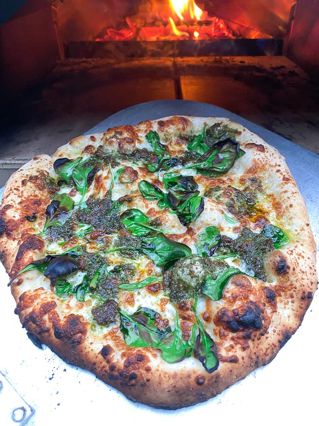 pesto spinach pizza on peel in front of wood fired Ooni oven