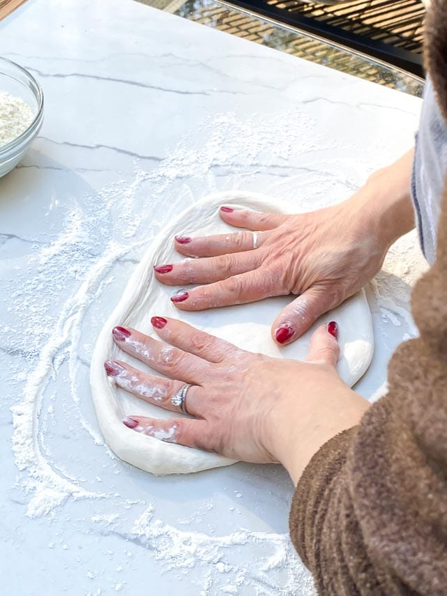stretching pizza dough with two hands
