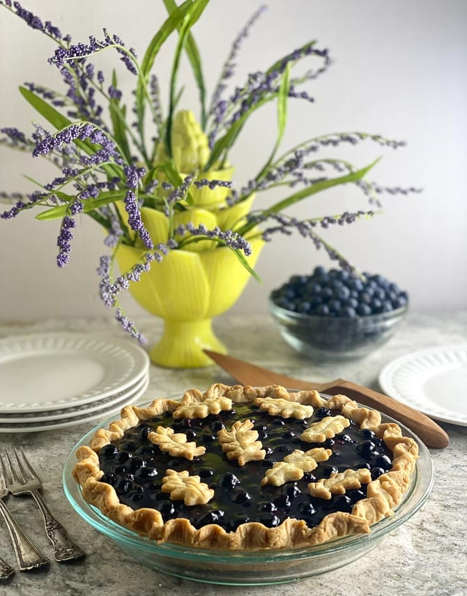 vertical of low FODMAP Fresh Blueberry Pie on gray quartz and white plates