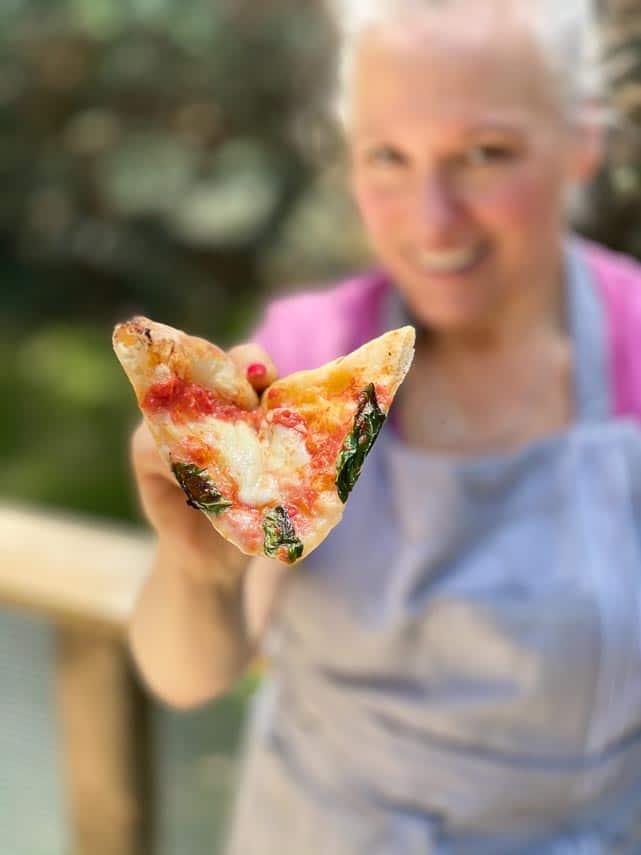 woman holding pizza toward camera