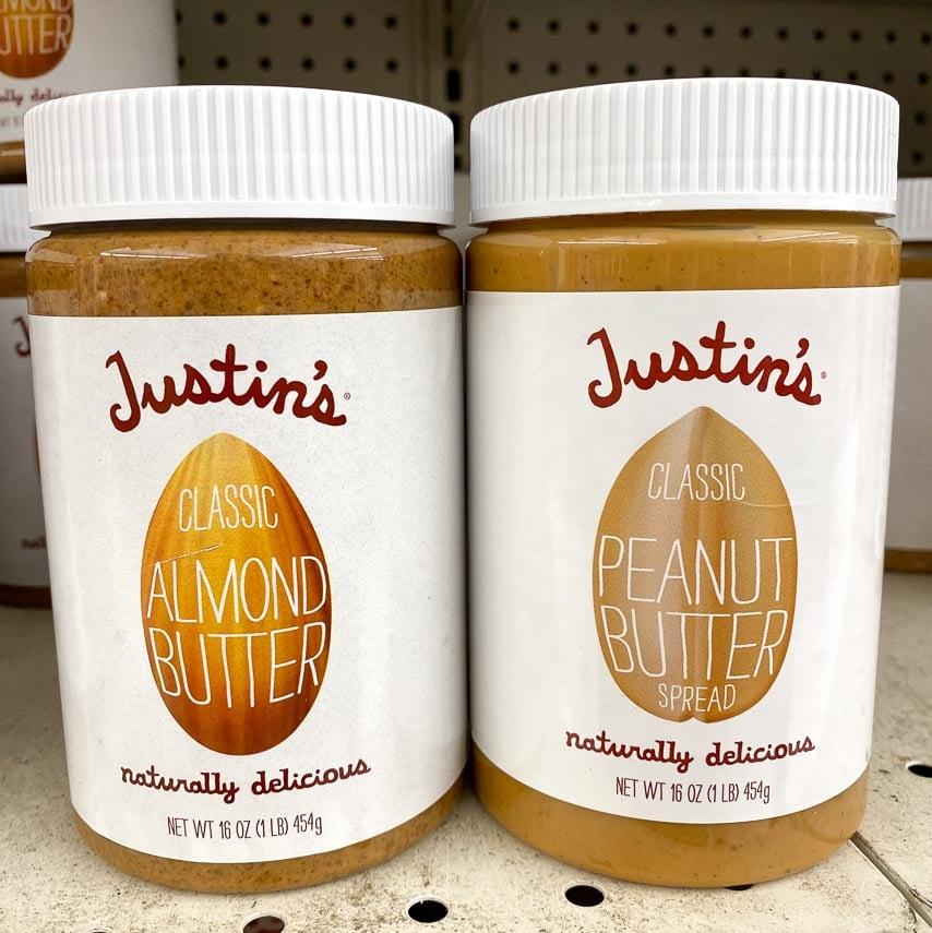 Justin's almond butter and peanut butter jars on supermarket shelf