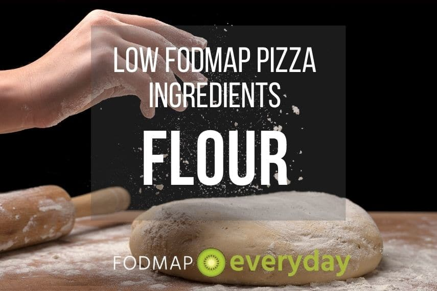 A hand dropping flour upon a large piece of kneaded pizza dough