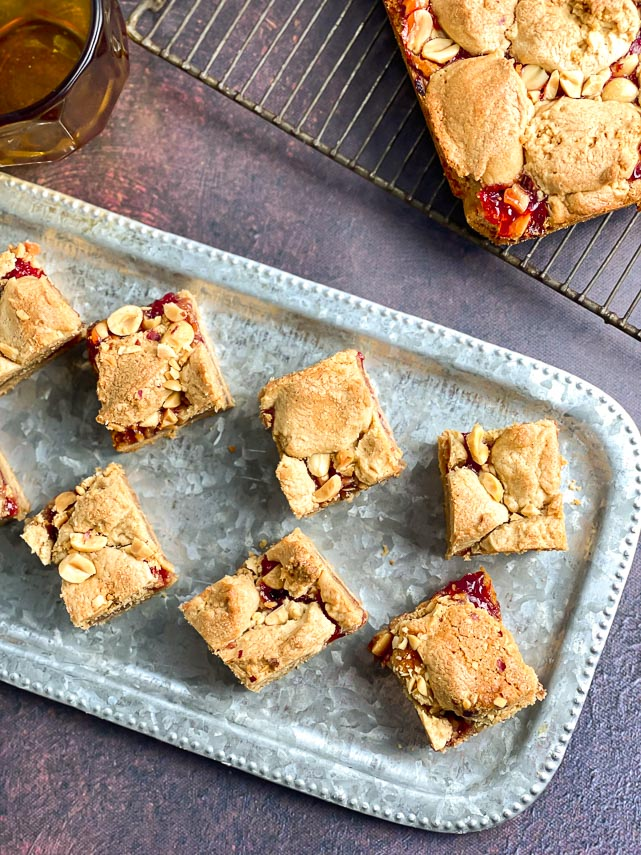 closeup of peanut butter and jelly bars on silver tray, cut into squares