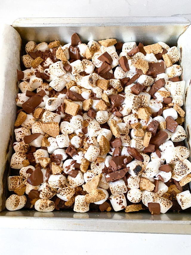 mini-marshmallows-graham-crackers-and-chocolate-scattered-on-top-of-brownies-in-square-pan-browned-with-torch