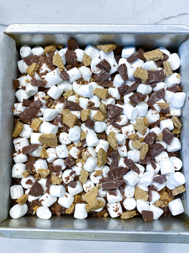mini marshmallows, graham crackers and chocolate scattered on top of brownies in square pan