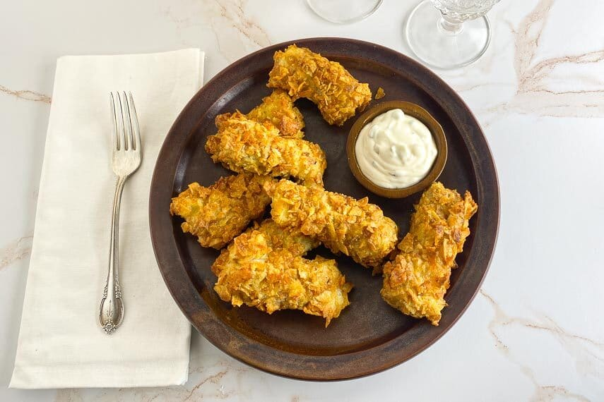 overhead air fryer low FODMAP fish sticks on marbled background and brown plate