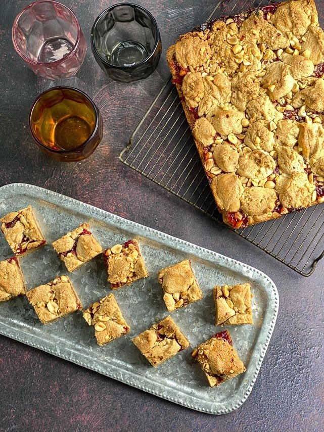 overhead vertical image of peanut butter and jelly bars on rack and silver tray