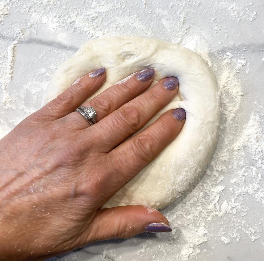 patting out sourdough pizza round