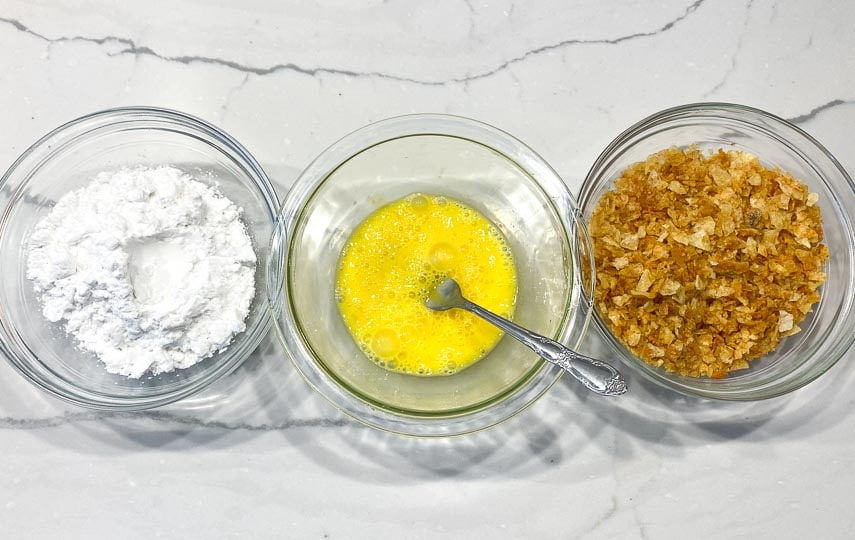 set up for making fish sticks- left to right in glass bowls, potato starch, beaten eggs and crushed potato chips
