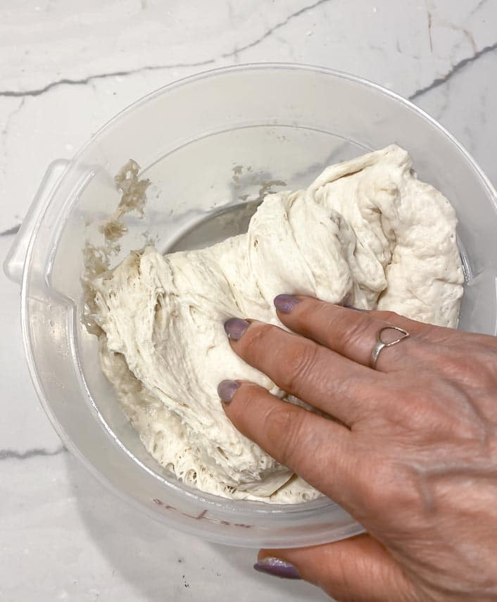 stretching and folding dough in container