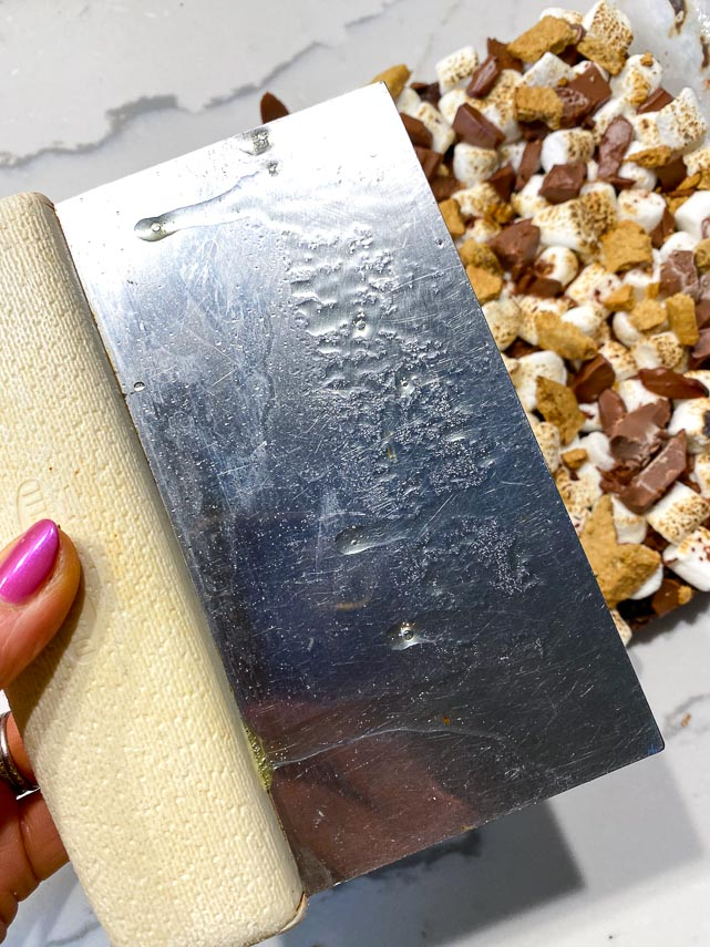 using a nonstick spray coated bench knife to cut s'mores brownies