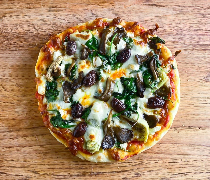 Low FODMAP sourdough pizza topped with vegetables on board