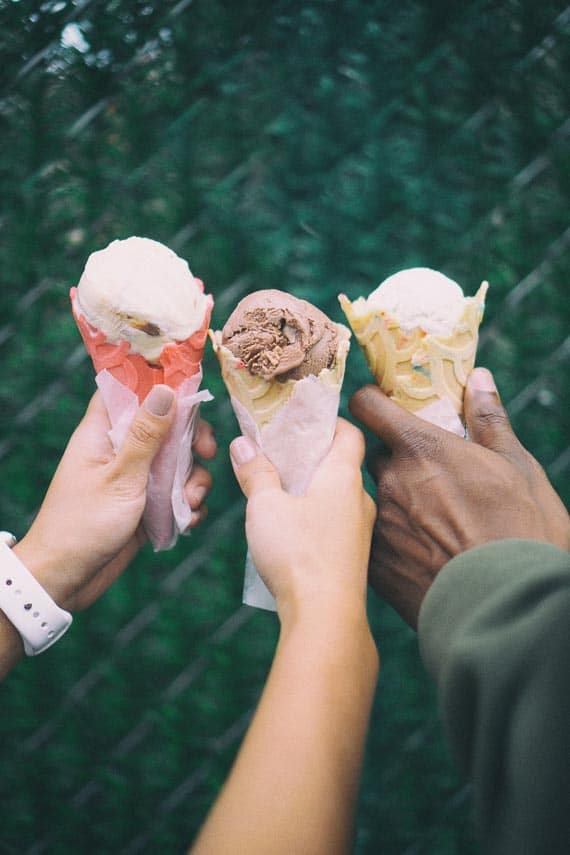 3 hands holding ice cream cones outdoors