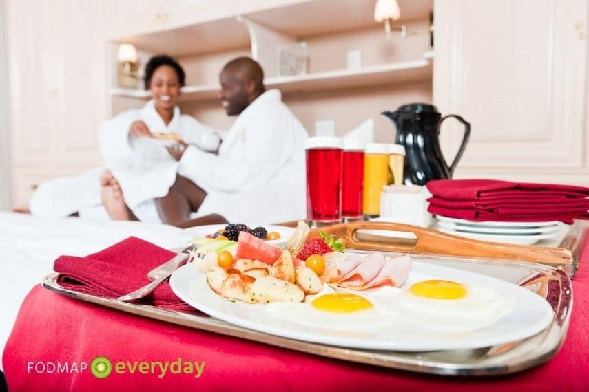 A man and a woman enjoying meal service in their hotel room