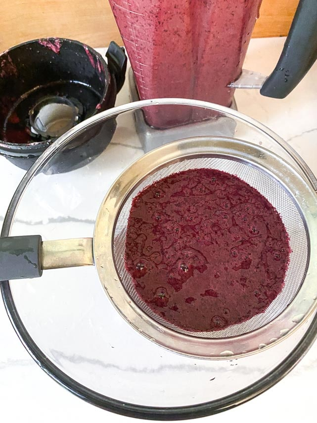 blueberry purée in fine mesh strainer set over glass bowl